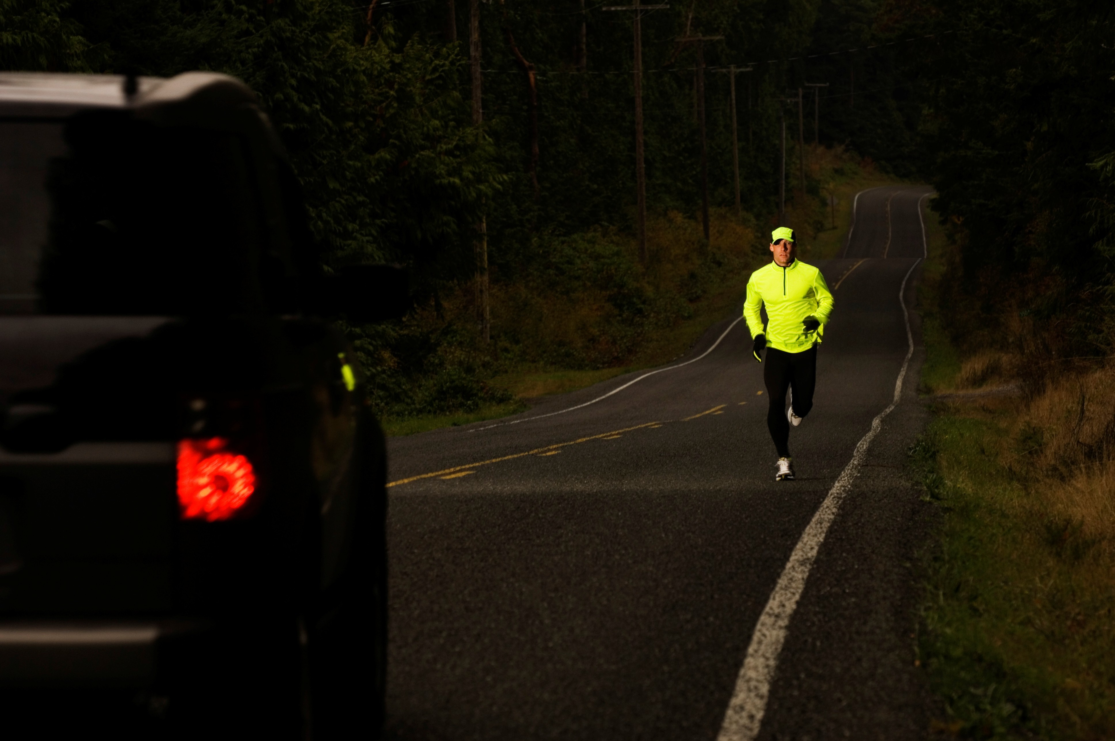 Man jogging on road, car approaching, dusk