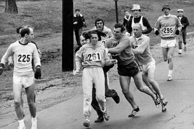 "BOSTON, MA - APRIL 19: Kathrine Switzer, of Syracuse, N.Y., center, was spotted early in the Boston Marathon by Jock Semple, center right, who tried to rip the number off her shirt and remove her from the race. Switzer's friends intervened, allowing her to make her getaway to become the first woman to ""officially"" run the Boston Marathon on April 19, 1967. (Paul Connell/The Boston Globe via Getty Images)"